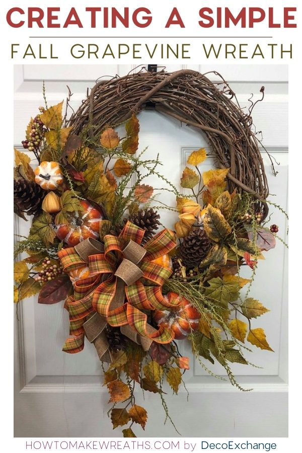 Grapevine wreath filled with fall decor pieces hanging on a white door.