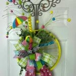 Yellow bike wheel with multi colored terri bow and greenery door hanger